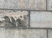 Sockelvåning i sten, huggen i olika tekniker.