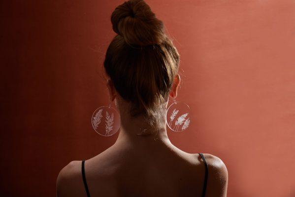 Fille avec des boucle d'oreille en plexiglas transparent gravé à la main de graminées