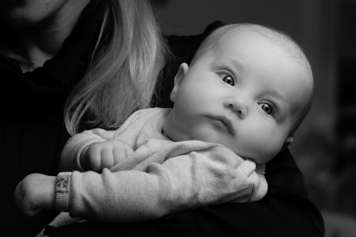 Mor med baby på armen i sort/hvid