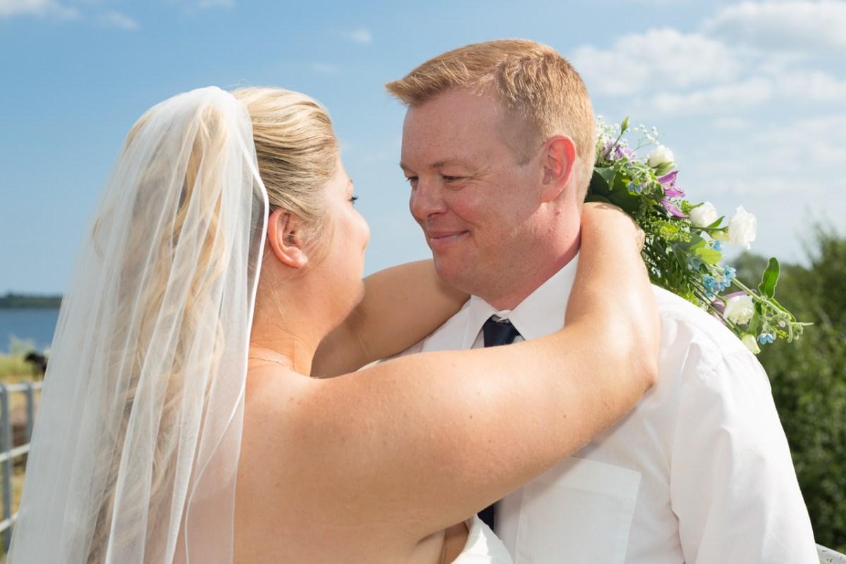 Bruden med armene om halsen på sin mand