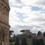 Colosseum fra top til bund i venstre side af billedet. Skyer og træer i baggrunden