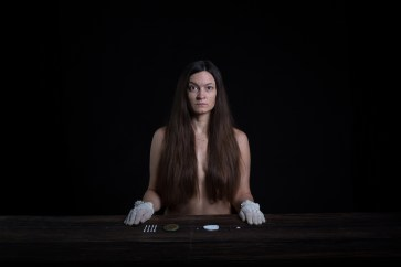 Sitting behind a desk with skin picking tools laid out, long hair covering the body