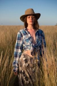 model med skovmandsskjorte og cowboyhat, gående mod kameraet