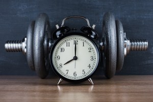 barbell on a gray background and retro alarm clock. Time 8:00