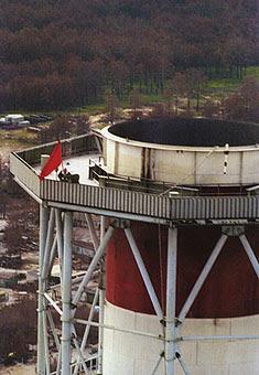 """Victoire ! Une banderole apposée sur le réacteur éventré proclame que """"le peuple soviétique est plus fort que l'atome"""" tandis qu'un drapeau rouge est fixé au sommet de la tour d'aération de la centrale à l'issue des travaux de déblaiement. [Tass]"""