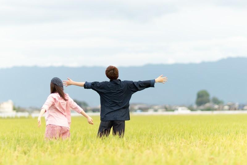 田んぼの中で手を広げて深呼吸する男女