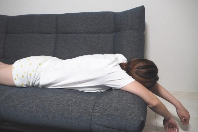疲れてうつ伏せにソファーに横たわっている女性