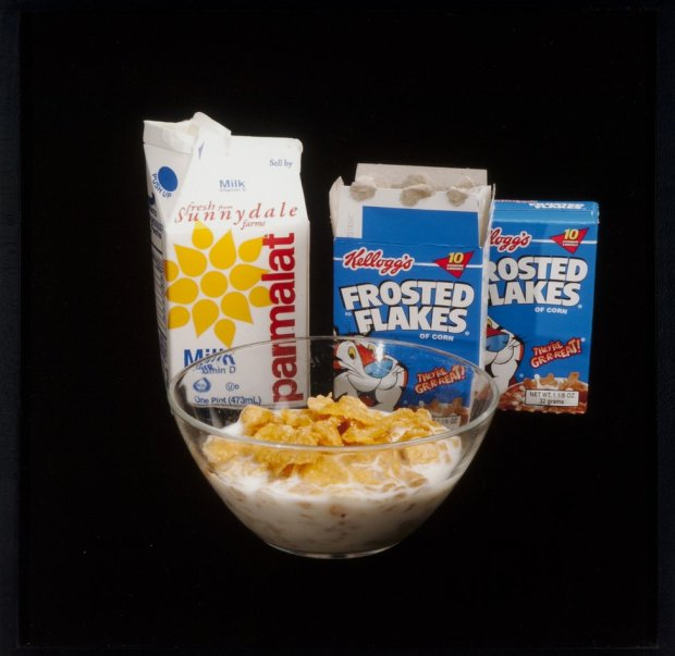 A bowl of cereal with milk, a milk carton and two packets of Frosted Flakes