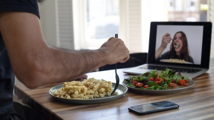 A man and a woman having dinner through a video call.