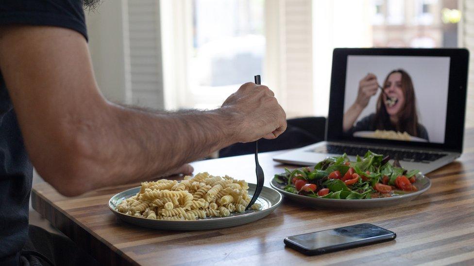 A man and a woman having dinner through a video call.