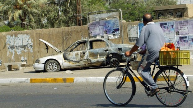 An Iraqi man rides a bicycle past the remains of a car burnt during a deadly incident involving Blackwater guards in Baghdad in September 2007