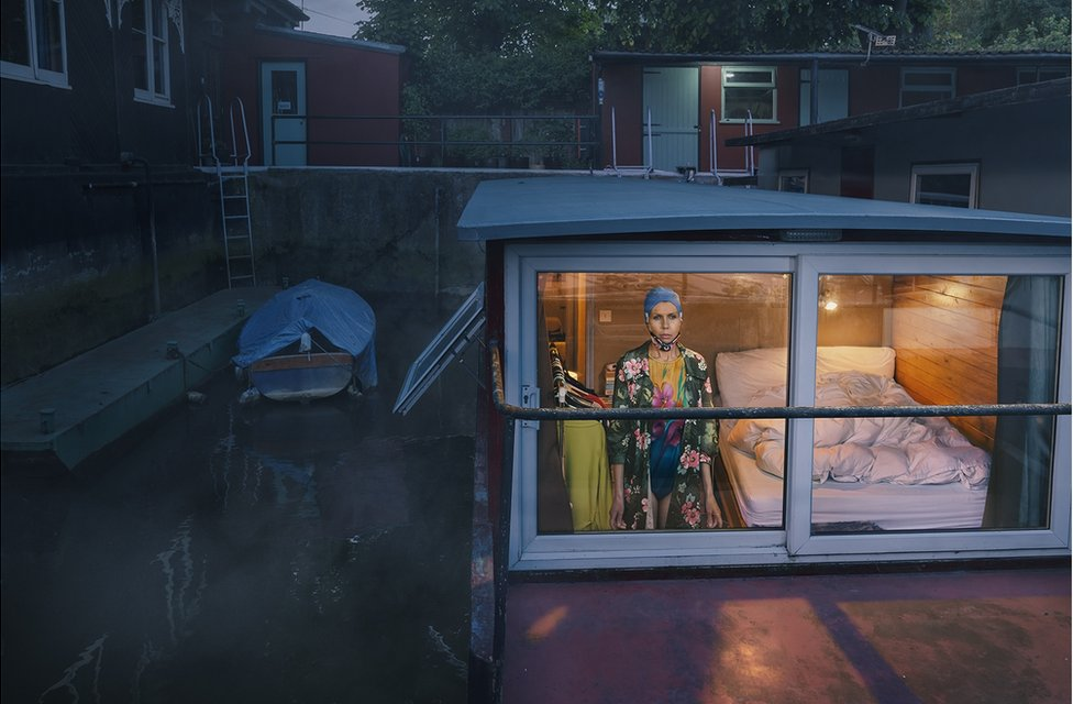 A woman looking out of the window of a house boat