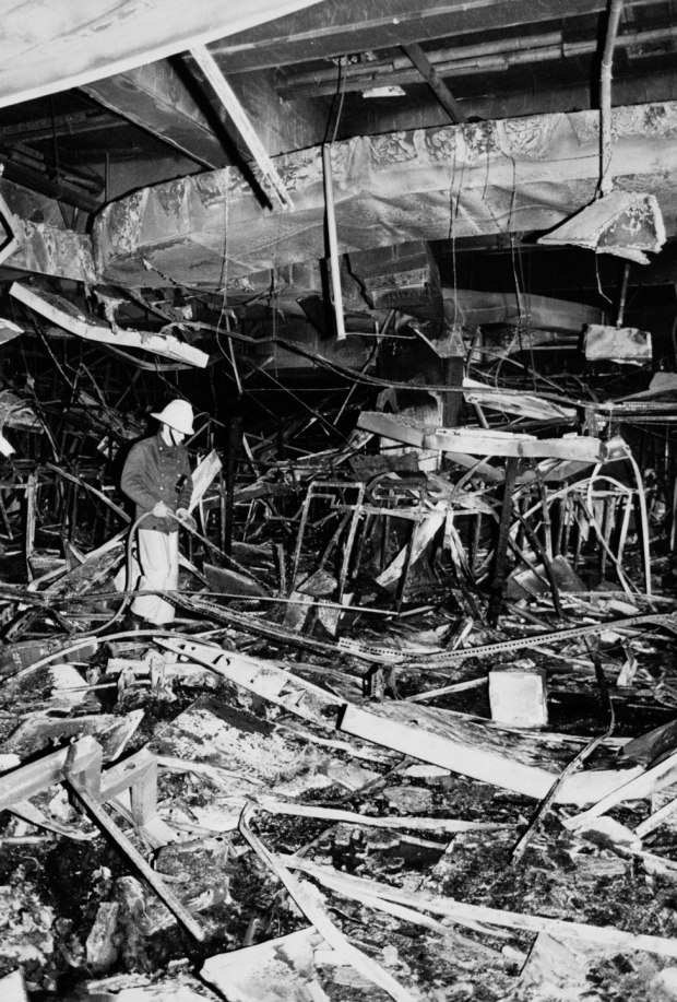 A fireman hoses down the remains of a gutted building