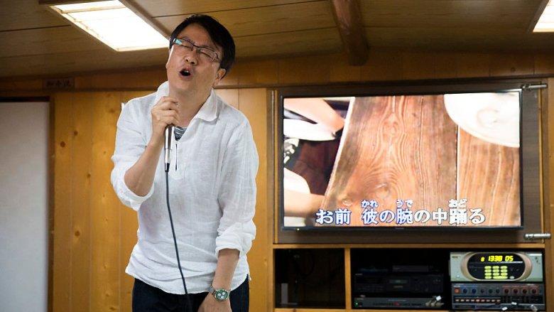 Un japonés canta una canción en un karaoke.