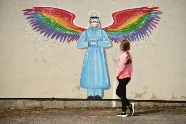 A girl walks past a mural of a doctor with rainbow angel wings
