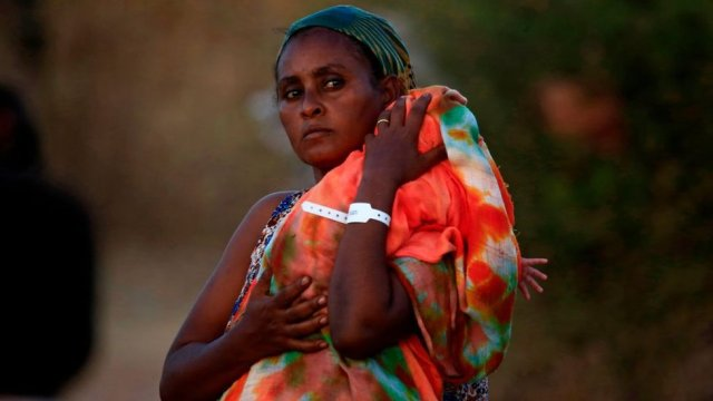 An Ethiopian refugee who fled fighting in Tigray province carries her baby as she walks at the Um Rakuba camp in Sudan's eastern Gedaref province