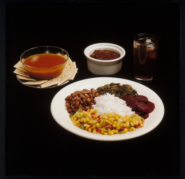 A meal featuring, beans, rice, sweetcorn, crackers and cola