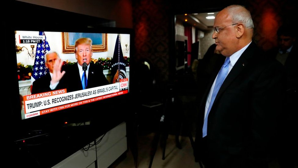 Saeb Erekat staring at Donald Trump on a screen