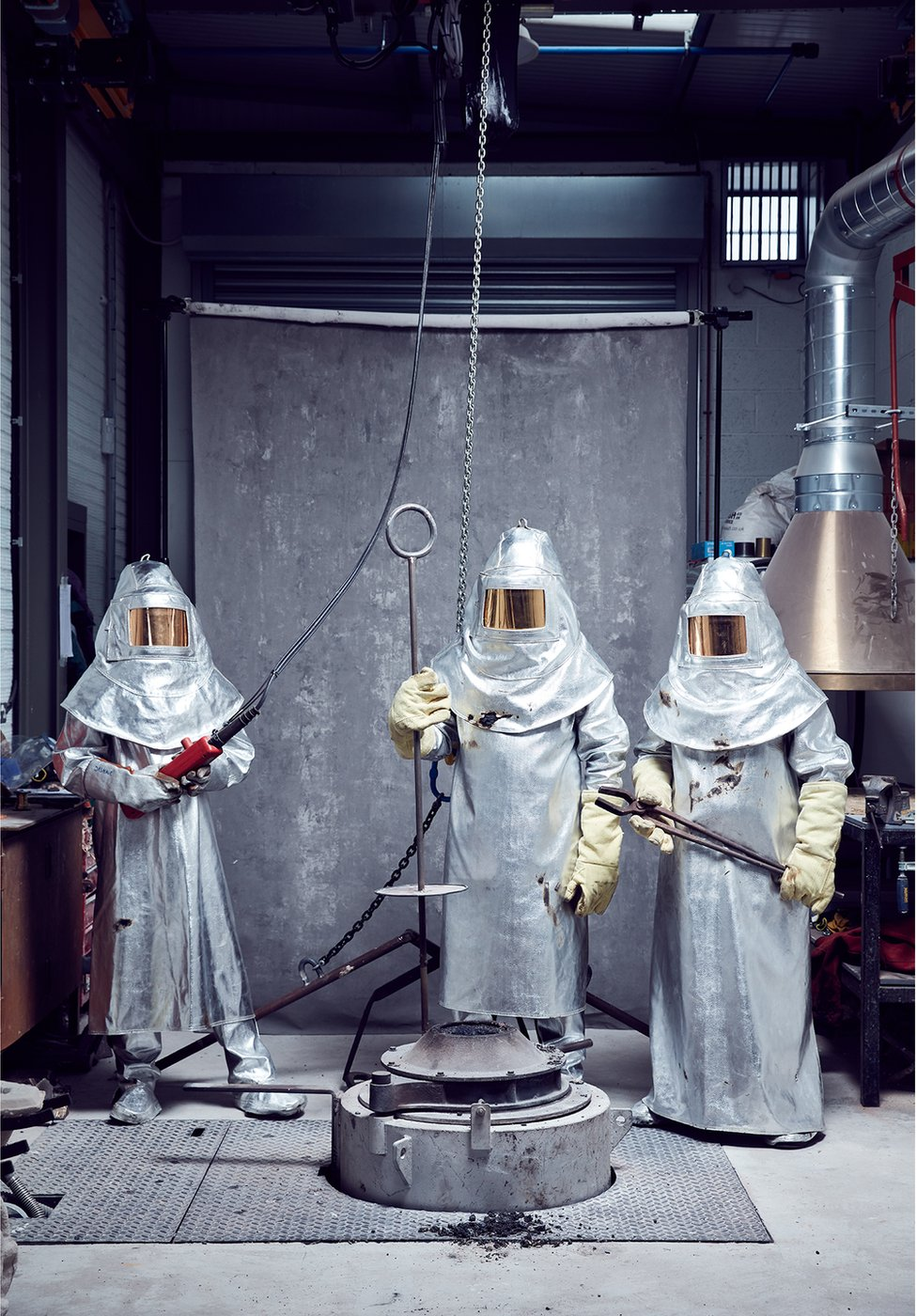 Three metal forgers stand in their protective equipment