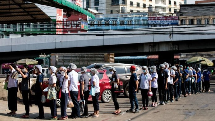People queue to be tested for Covid-19 at a seafood market in Samut Sakhon on December 19, 2020