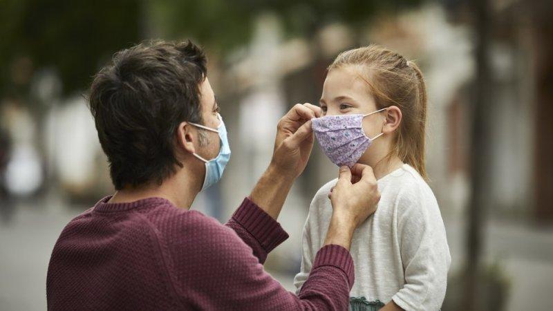 Man adjusting the mask on a girl