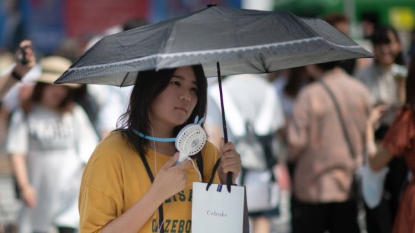 Una mujer usa un ventilador portátil para combatir el calor en Japón.