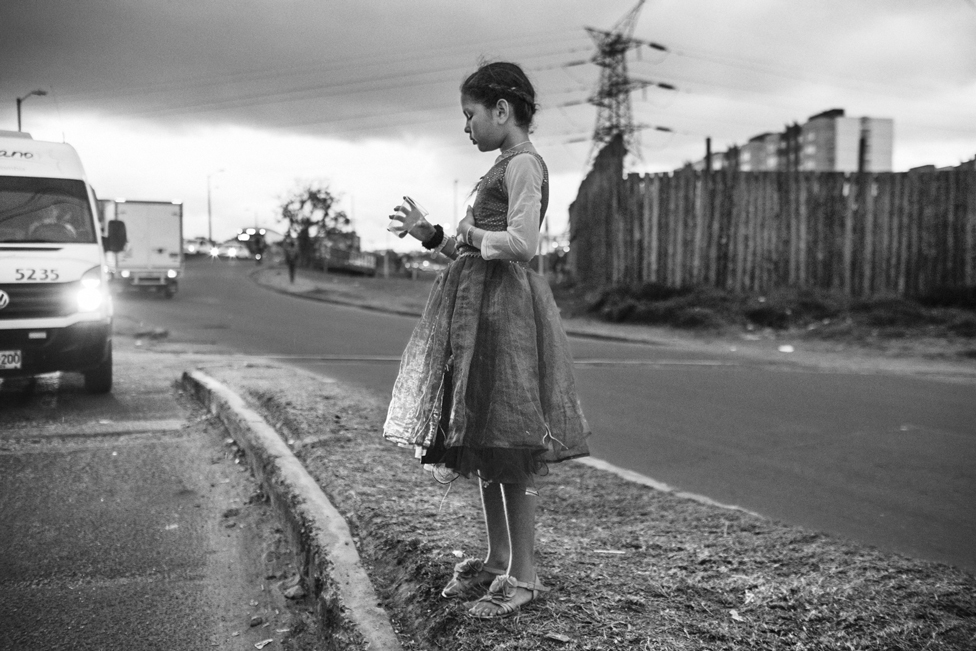 Black and white image of a child standing at the side of a road