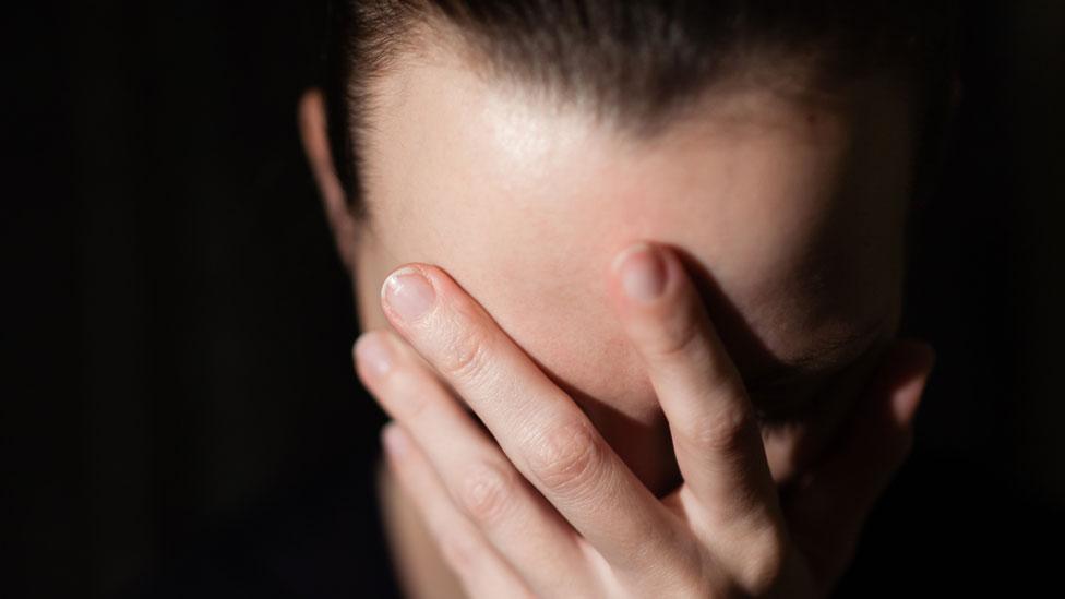 Mujere con el rostro cubierto por sus manos