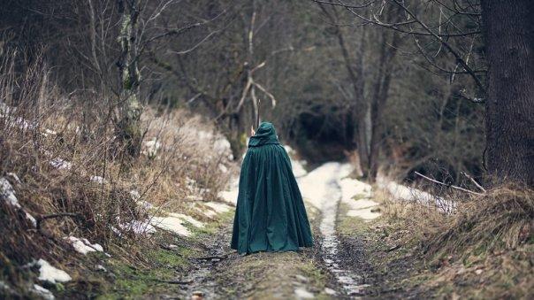 Persona con capa verde caminando sola en un bosque.