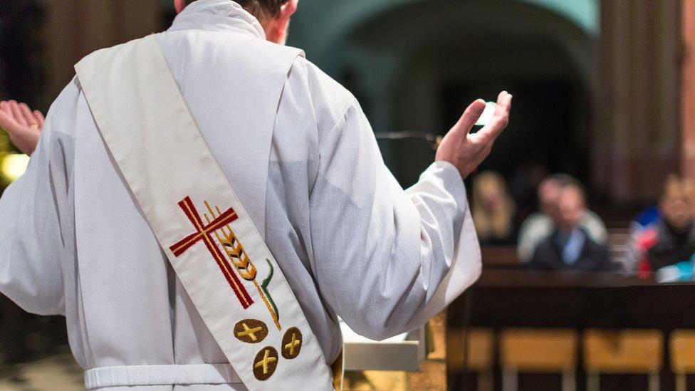 Un sacerdote de espaldas, predica a su congregación