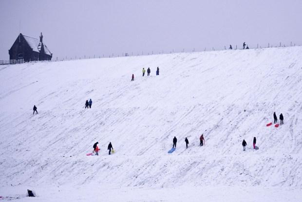 People sledge down a hillside at Butterley Reservoir in Marsden, West Yorkshire, on 14 January 2021
