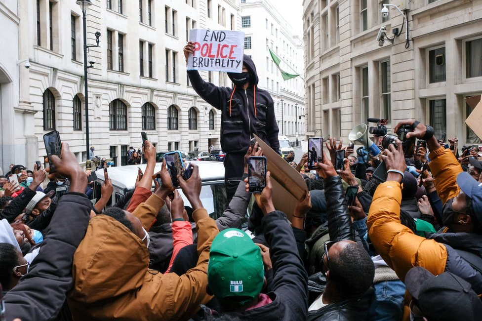Protesters take photos of Wizkid outside the Nigeria High Commission on 11 October.