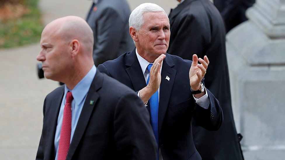 U.S. Vice President Mike Pence reacts to supporters outside the New Hampshire State House as he walks near his Chief of Staff Marc Short