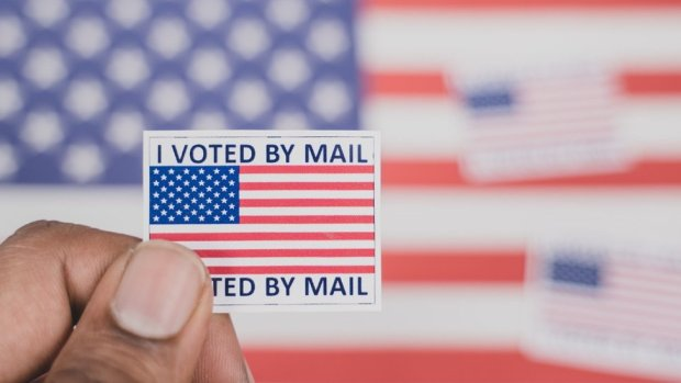 Man holding a 'I voted by mail' sticker