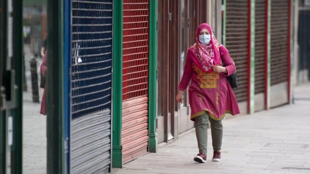 Woman in facemask walks past closed Cardiff shops