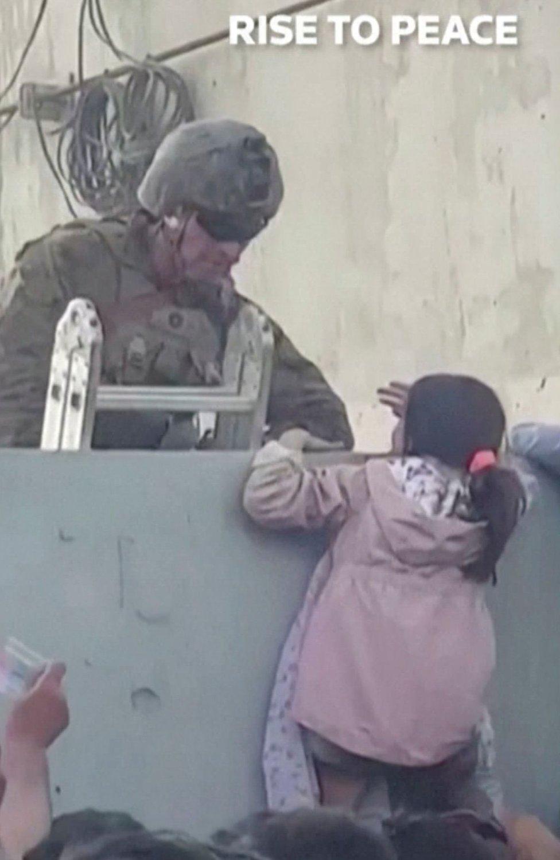 Una niña recibe asistencia para subir el muro del aeropuerto de Kabul