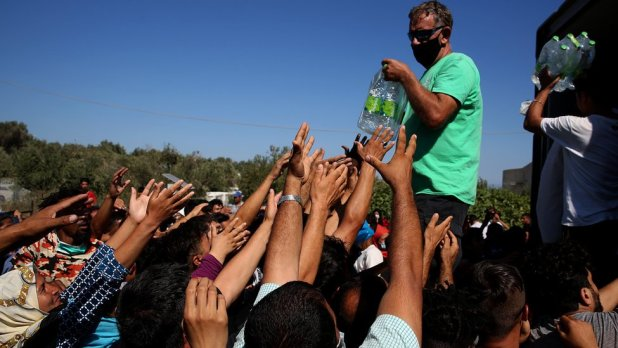 Migrants receive food, fruit and water near Moria Camp on Lesbos Island, Greece, 10 September 2020