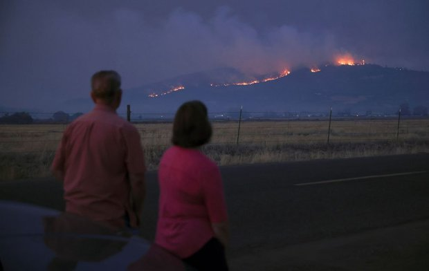 Local residents look at smoke and fire over a hill during wildfires near the town of Medford, Oregon, 9 September 2020