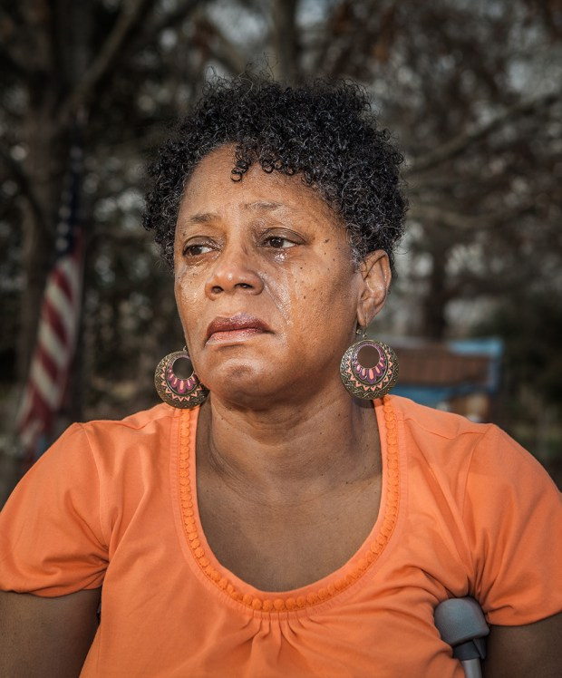 Antoinette Harrell outdoors, with tears running down her face