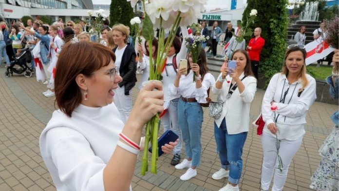 Representative of the Co-ordination Council for members of the Belarusian opposition Olga Kovalkova holds flowers as she attends an opposition demonstration to protest against presidential election results in Minsk, Belarus August 22, 2020.