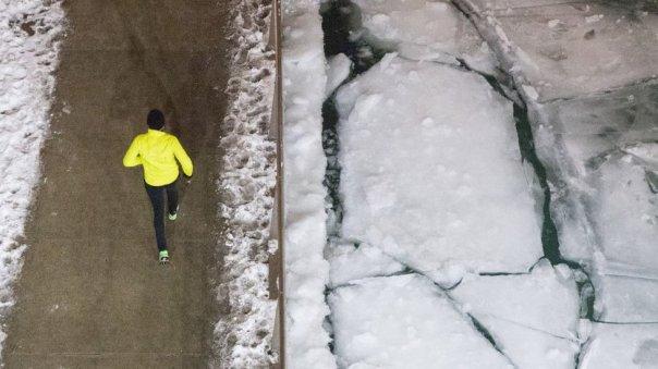 Personas corriendo junto a bloques de hielo en Chicago