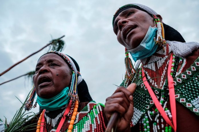 Women, wearing beaded clothing, sing and march during the festivities.