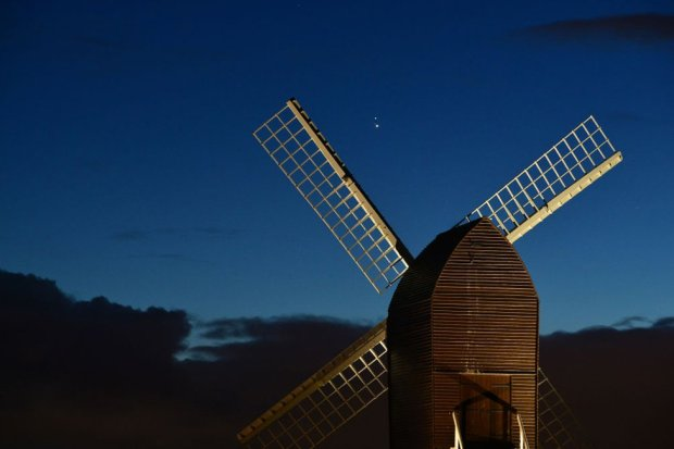 Jupiter and Saturn are seen coming together in the night sky, over the sails of Brill windmill, England. 20 December 2020