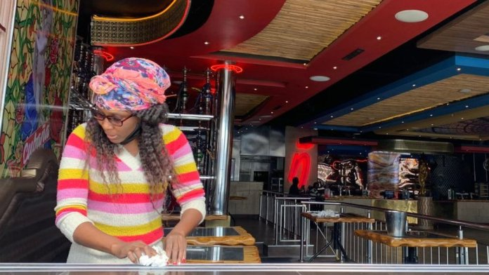 A woman cleaning a table in bar in Johannesburg, South Africa - August 2020