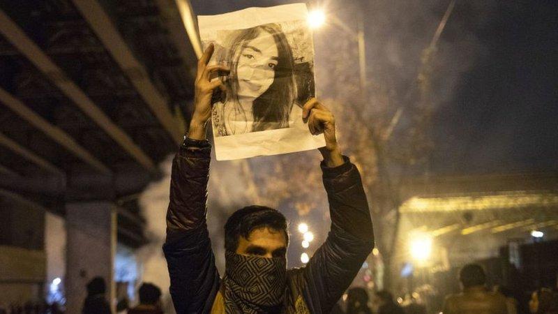 Un manifestante en Irán con la imagen del rostro de una mujer.