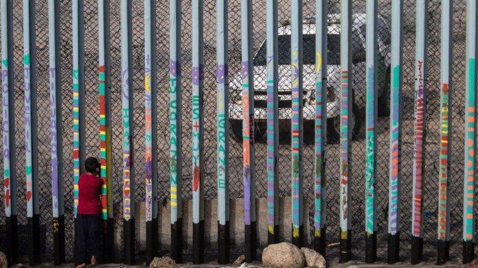 Niño mira un vehículo de la Patrulla Fronteriza en la frontera entre Estados Unidos y México en Tijuana.
