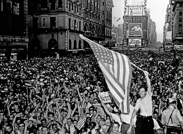 A crowd cheering with a man waving an American flag