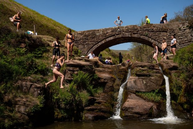 People enjoying the good weather by Three Shires Head on the River Dane, where Cheshire, Derbyshire and Staffordshire meet. 31 March 2020