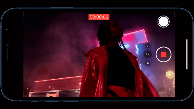 An iPhone is shown shooting a challenging scene at night with backlit neon lights