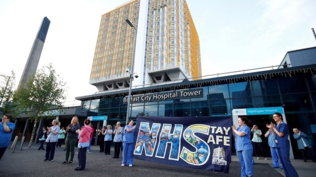 NHS workers with a banner react at the Nightingale Hospital during the Clap for our Carers campaign in support of the NHS in May
